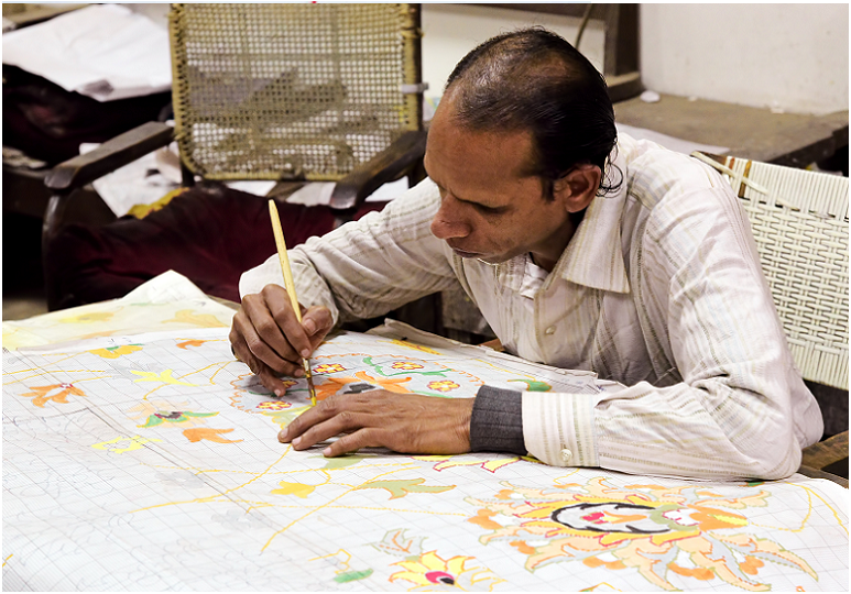 Indian man creates a wool carpet design. These design motifs have been handed down from generation to generation in Agra, India.