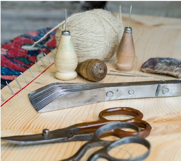 Hand tools for preparing and restoring rugs, including brush.