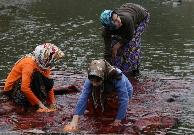 Iranian women washing a hand-woven carpet in a lake.