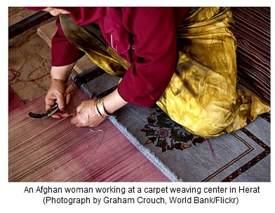 An Afghan woman working at a carpet weaving center in Herat
