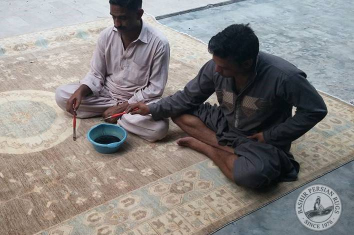 Pakistani rug artisans using their paint brushes to  perform some minor color touch ups with vegetable dyes on a hand-knotted Oushak style rug.